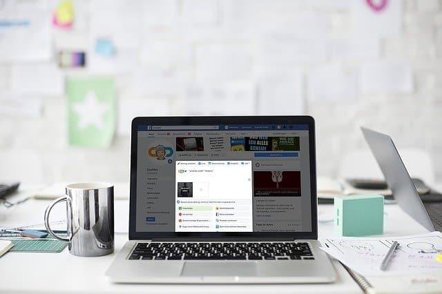Auf einem Laptop ist die Unternehmensseite bei Facebook geöffnet und ein Beitrag markiert
